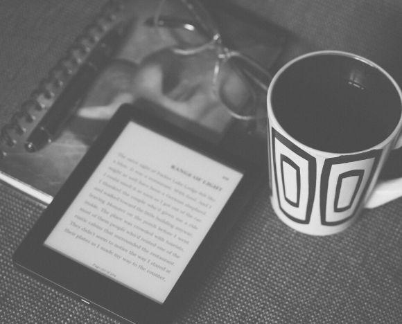 Un ebook ouvert sur une tablette, à côté d'une tasse de café