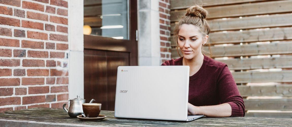 Une jeune femme travaille dehors sur son ordinateur portable