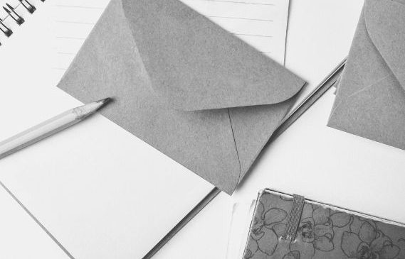 Des enveloppes et des carnets posés sur un bureau