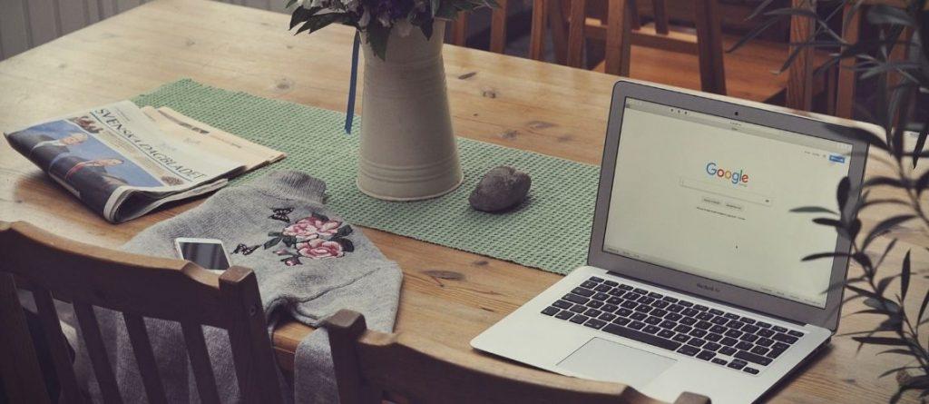 Un ordinateur portable est posé sur une table et montre l'écran d'accueil de Google