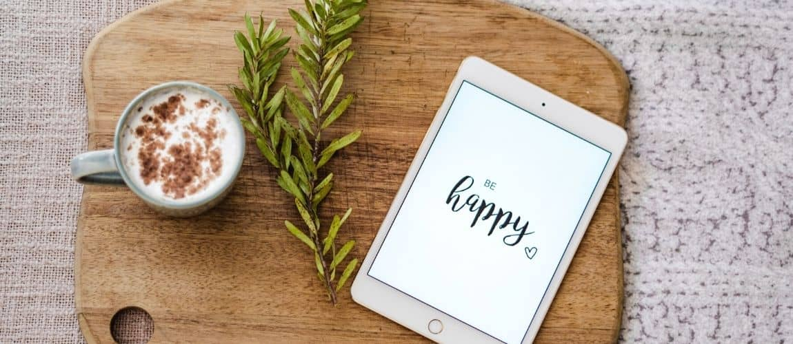 """une tablette qui affiche le message """"happy"""" pour donner le sourire à une entrepreneuse qui cumule salariat et freelancing"""